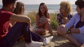 Group Of Young People Sitting On The Sandy Beach. Young gang of five people sitting on the sandy beach and enjoy leisure time on the beach while discussion stock video footage