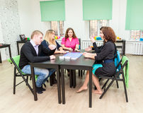 Group of young people sitting at table and playing games Royalty Free Stock Photo