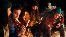 Group of young people sitting in winter forest by the fire. Frying different types of food