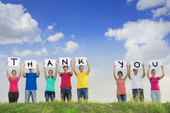 Group of young people spelling thank you. Group of young people holding papers with the words thank you stock images