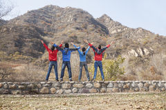 Group of young people standing on the ledge, arms outstretched Stock Photos