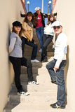 Group of young people standing on stairs. Group of five young people standing on the stairs in a bright summer day Royalty Free Stock Image