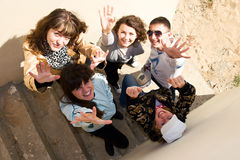 Group of young people standing under stairs. Group of five young people standing under the stairs, throwing hands in the air Royalty Free Stock Image