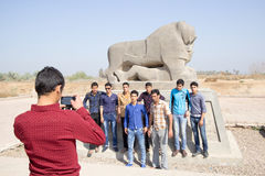 A group of young people taking a picture with the lion of Babylo Stock Photo
