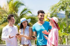 Group Of Young People Talking Holding Cell Smarrtphones Over Green Tropical Forest Landscape Mix Race Men And Women Royalty Free Stock Photo