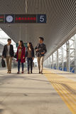 Group of young people talking on railway platform Stock Photo