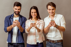 Group of young people. Technology and internet concept: group of young people looking at their smartphones, on a gray background Royalty Free Stock Image