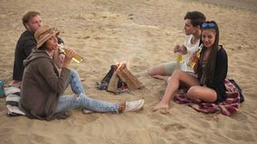 Group of young people toasting with beer bottles and having a beach party on a summer day saying cheers with beer in 4k.  stock footage