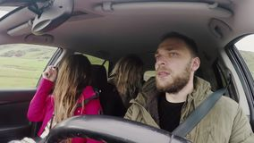 Group of young people traveling by car and eating something sitting inside. Friends going to trip together. stock footage