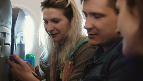Group of young people traveling by plane. Two woman and man sitting near the window and looking photos on smartphone. stock video