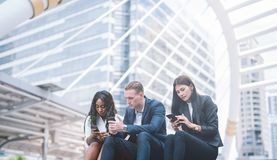 Group of young people use their phones in city. stock images