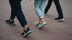 A group of young people walking around the city. Close-up legs. Side view. Cinematic shots stock footage