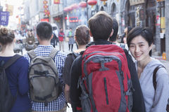 Group of young people walking down street, woman looking over shoulder. Royalty Free Stock Photo