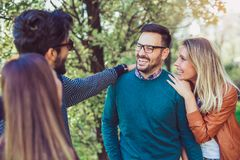 Group of young people walking through park. Stock Photos