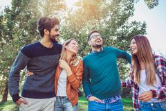 Group of young people walking through park. Royalty Free Stock Image
