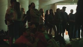 Group of young people watching show and cheering inside a tent. Colorful lights. Group of young people watching show, cheering and applauding inside a tent stock video