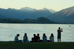 Group of young people watching sunset at lake Wanaka Royalty Free Stock Image