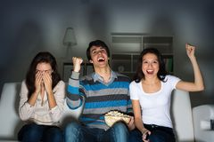 Group of young people watching TV on the couch. Sports fans Royalty Free Stock Image
