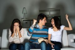Group of young people watching TV on the couch Stock Photos