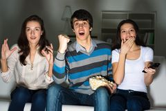 Group of young people watching TV on the couch Stock Image