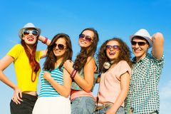 Group of young people wearing sunglasses and hat. S hugging and standing in a row, spending time with friends Stock Photography
