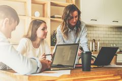 Group of young people working together.Man is using laptop,girls looking on screen of laptop,discussing business plan. Royalty Free Stock Photography