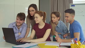 Group of young people works at the office. Group of young caucasian people working together at the office. Attractive men and women looking at the laptop screen stock video footage