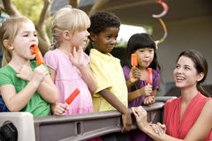 Group of young preschool children playing. Diverse group of preschool 5 year old children playing in daycare with teacher stock photography