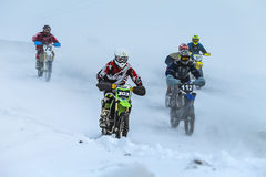 Group young racers drive on snowy motocross track Royalty Free Stock Photos