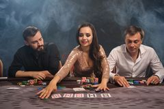 Group of a young rich friends are playing poker in casino. Group of a rich excited friends are playing poker at casino in smoke. Youth are making bets waiting stock image
