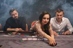 Group of a young rich friends are playing poker in casino. royalty free stock image