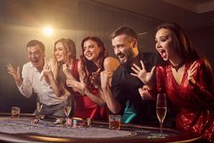 Group of a young rich friends are playing poker in casino. royalty free stock photography