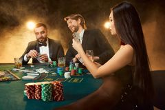 Group of young rich people is playing poker in the casino. Two men in business suits and a young women in a black dress. Smoke. Casino. Poker Stock Photos