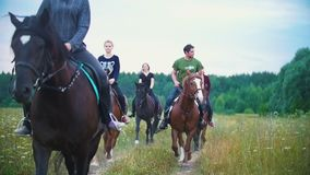 Group of young riders on horseback galloping by the pathway