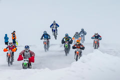 Group young riders on motorcycles are driving snow-covered motocross track Stock Image