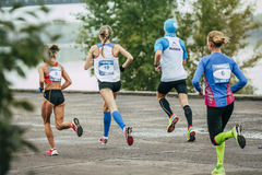 Group of young runners run along embankment of river Royalty Free Stock Image
