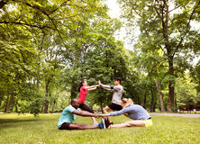 Group of young runners stretching and warming up in park. Stock Image