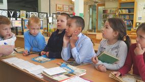 A group of young schoolchildren stand with books at the table. Chapaevsk, Samara region, Russia - May 10, 2019: Elementary school of the city of Chapaevsk. A stock video