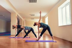 Group of young slim women stretch in yoga class stock photography