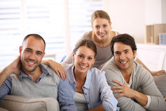 Group of young smiling people on sofa Stock Images
