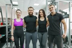Group of young smiling sport people embracing together in fitness gym. Fitness, sport, teamwork, motivation, people, healthy royalty free stock photo