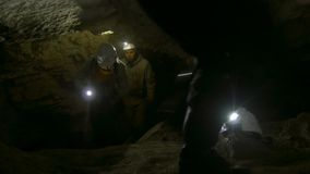 Group of young speleologists climb up in the dark narrow cave. Close up stock footage