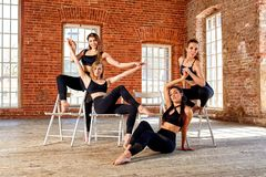 Group of young sports girls resting after a workout in a spacious loft studio. Female friendship in the gym, relaxing royalty free stock photos