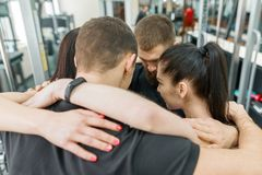 Group of young sports people embracing together in fitness gym backs. Fitness, sport, teamwork, motivation, people, healthy. Lifestyle concept stock images