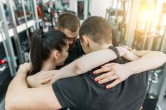 Group of young sports people embracing together in fitness gym backs. Fitness, sport, teamwork, motivation, people, healthy. Lifestyle concept royalty free stock photos