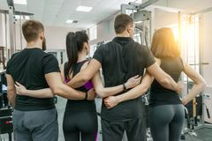 Group of young sports people embracing together in fitness gym backs. Fitness, sport, teamwork, motivation, people, healthy. Lifestyle concept stock image