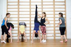 Group of young sports woman does an extension exercise at the Swedish wall Stock Photos