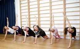 Group of young sports woman does an extension exercise at the Swedish wall Royalty Free Stock Photography