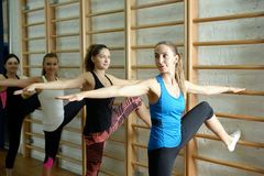 Group of young sports woman does an extension exercise at the Swedish wall Stock Photo