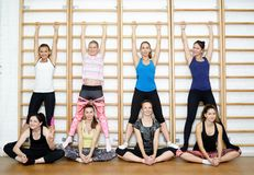 Group of young sports woman does an extension exercise at the Swedish wall Royalty Free Stock Image